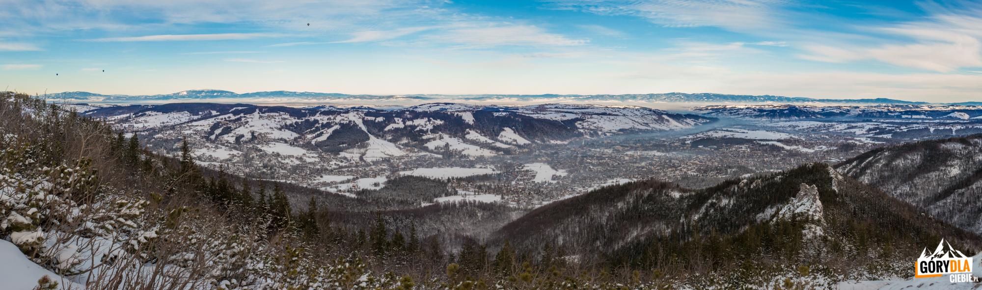 Widok zSarniej Skały (1377 m) nacałą dolinę Zakopanego, Gubałówkę, ana horyzoncie Pilsko, Babią Górę, Police, całe pasmo Gorców iPieniny