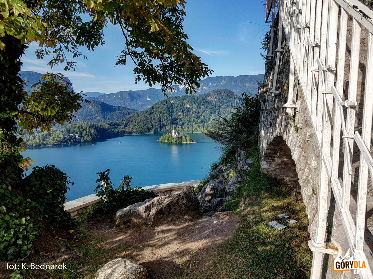 Widok zBledskiego Gradu najezioro Bled iwyspę Blejski Otok. Nawyspie stoi kościółek Maryi Wspomożycielki